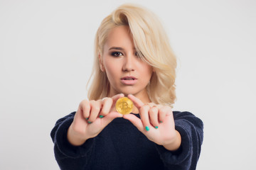 Portrait of a young blonde businesswoman wearing a black shirt, bitcoin
