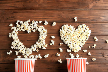 Composition with tasty popcorn on wooden background, top view