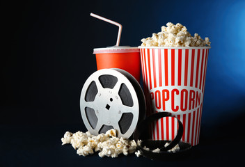 Movie reel, paper cups with popcorn and drink on dark background