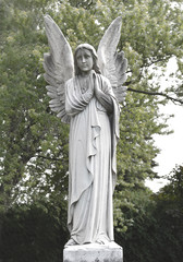 Vintage sad angel on a cemetery against the trees and leaves background. Holy angel.