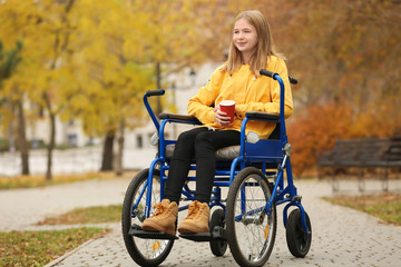 Little girl in wheelchair with cup of coffee outdoors