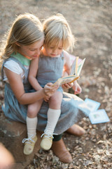 Young Girl and Boy Sit Reading Stories Outdoors