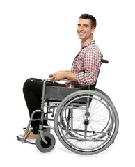 Young man in wheelchair on white background