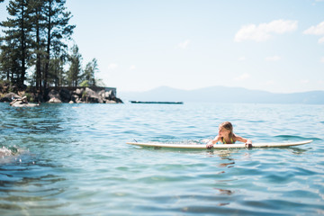 Young Girl Resting on Surfboard in Lake