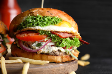 Tasty burger with fried egg on wooden board, closeup