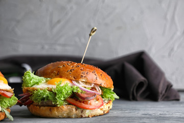 Tasty burger with fried egg on table