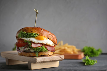 Tasty burger with fried egg on wooden board