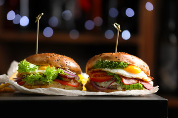 Tasty burgers with fried egg on table, closeup