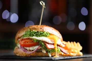 Tasty burger with fried egg on table, closeup