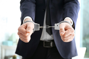 Businessman in handcuffs on blurred background