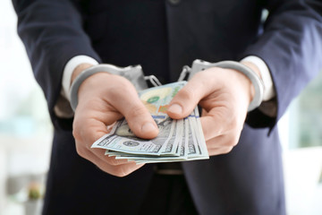 Businessman in handcuffs holding bribe on blurred background