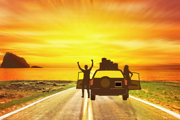 Young couple get out of the car to admire the place of their holidays at sunset.