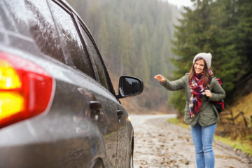 Female tourist hitchhiking car in countryside