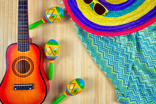 Mexico.Colored sombrero the guitar and maracas on a wooden background.