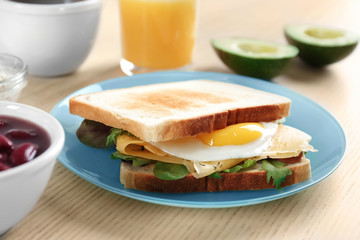 Plate with tasty toasts and fried egg on wooden table, closeup
