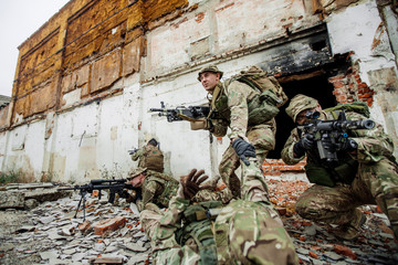 Special forces soldiers with weapons during the rescue operation. war, army, technology and people concept.