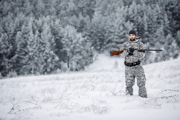 Male hunter in camouflage looking for his target or prey .Winter scene