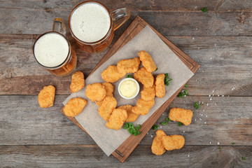 Tasty chicken nuggets, beer and sauce on table