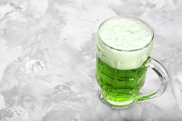 Glass of green beer on grey background. Saint Patrick's day celebration