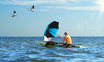 On the paddle board, catching the wind with an umbrella floats a teenager on the sea