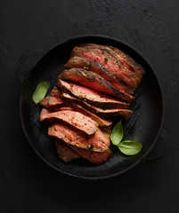 grilled steak in a frying pan on a wooden background