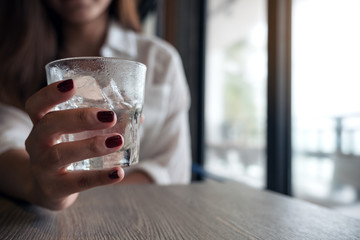 Closeup image of woman's hands with red nails color holding a glass of cold water