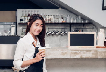 Asian female barista wear jean apron holding take away cup at machine counter bar with smile face,cafe service concept.making coffee.