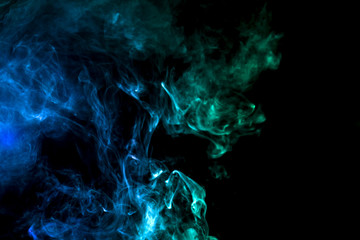 Dense multicolored smoke of blue, green on a black isolated background. Background of smoke vape