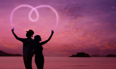 Love Concept, Silhouette of Couple using Smart Phone to making Romantic Heart Shape at Twilight Sea, Valentines Day Background