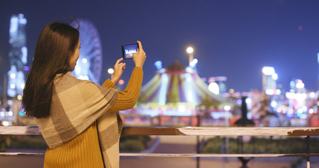 Woman taking photo on cellphone in night view
