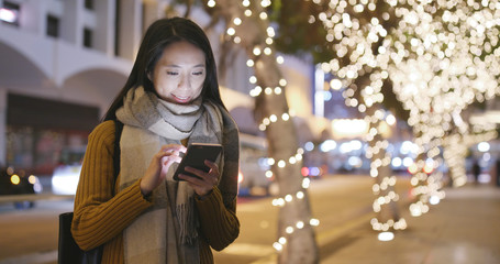 Asian Woman working on cellphone in the city at night Fotomurales