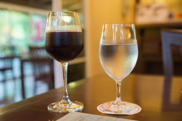 Glass of wine and a glass of cold water is placed on a wooden table in a restaurant at Valentine's Day of Couple of Love.