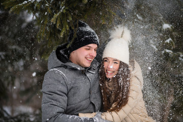 Cheerful teens having fun in snowy forest