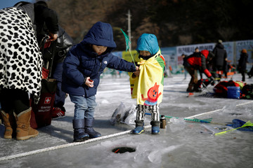 Children fish for trout on a frozen river during the Ice Festival in Hwacheon