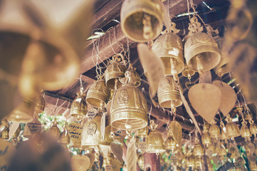 Golden bells in a buddhist temple. Toned image with a vintage effect look.