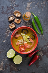 Spicy thai green curry soup on a brown stone background, vertical shot, top view