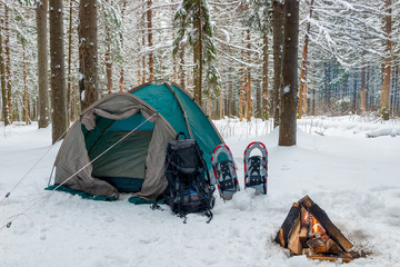 closed tent in the snow in the winter forest and a fire, no people