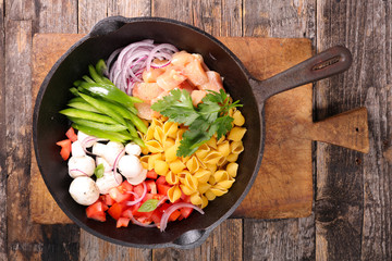raw pasta and ingredient on pan