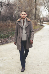 Handsome elegant man in the park wear suit and coat.