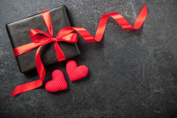Gift box and two crochet heart on black background