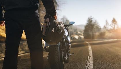 Motorradfahrer mit Motorrad auf einer Straße