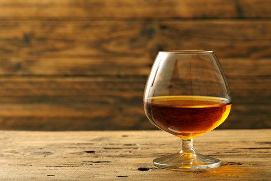 cognac o brandy bicchiere con bevanda alcolica su sfondo legno rustico