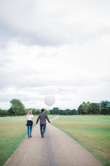 Back view of the young happy romantic couple in love who walking outdoor and boyfriend holding balloon in hand