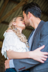 Portrait of young adorable beautiful couple in love who standing in embrace indoor and kissing