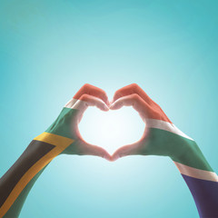 South Africa flag on woman hands in heart shape isolated on mint background for national unity, union, love and reconciliation concept.