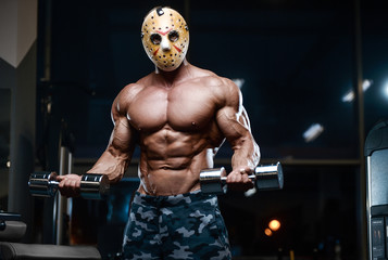 horror brutal Jason mask man strong bodybuilder athletic fitness man in scary hockey mask in the gym