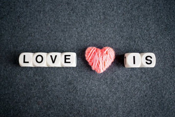 LOVE IS text word made with white plastic blocks and pink thread heart on grey felt background. Love, romance, Valentine's day concept