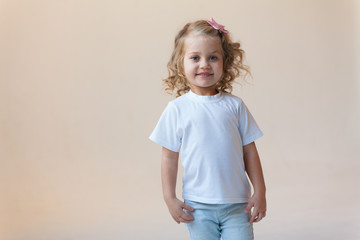 Cute little girl in a white t-shirt on a light background. Mock-up.
