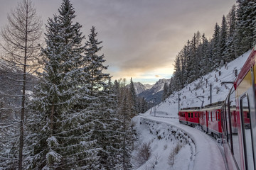 Red train in the snow in swiss alps