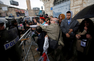 Palestinian security forces push away demonstrators from the convoy of Greek Orthodox Patriarch of Jerusalem Theophilos III, during a protest against his visit, in the West Bank city of Bethlehem